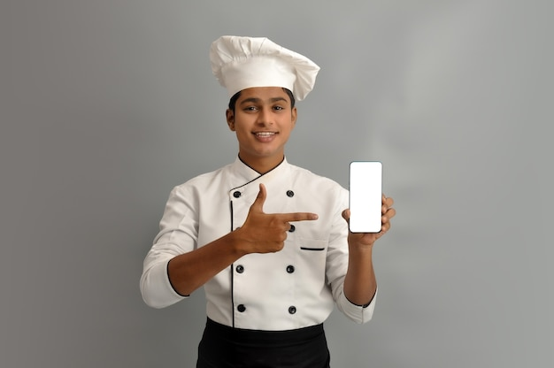 Portrait of a happy male chef dressed in uniform holding mobile and pointing