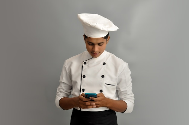 Portrait of a happy male chef dressed in uniform holding mobile and sending sms or chatting