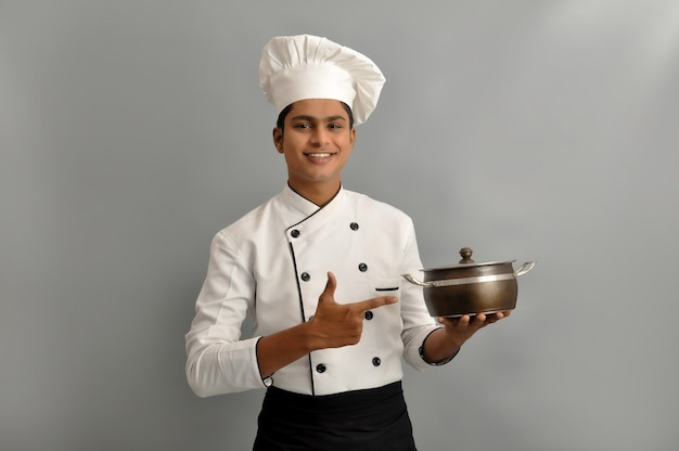 Portrait of a happy male chef dressed in uniform holding pot and pointing