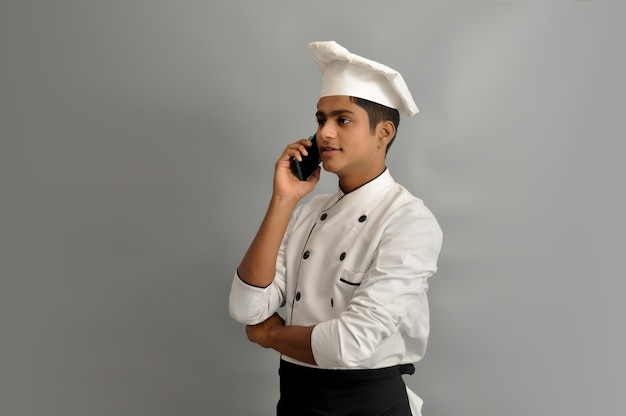 Portrait of a happy male chef dressed in uniform talking on phone