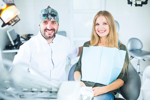 Portrait of happy male doctor with female patient