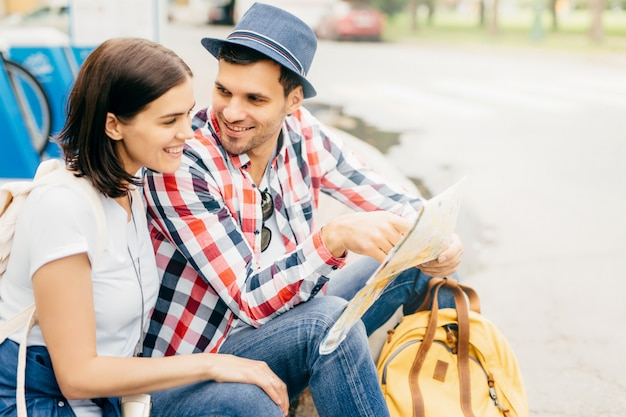 Portrait of happy male and female friends, having trip, resting on park bench, looking happily into map, choosing place where to go. young tourists having vacation using city map. relaxation concept