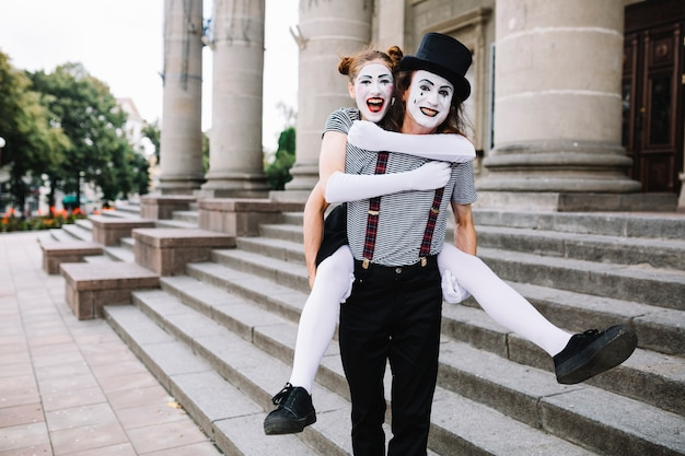 Portrait of a happy male mime giving piggyback ride to female mime