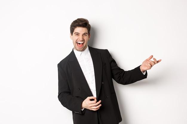 Ritratto di uomo felice che balla alla festa, suona la chitarra invisibile e ride, in piedi in abito nero su sfondo bianco.