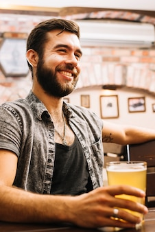 Portrait of a happy man drinking beer in bar
