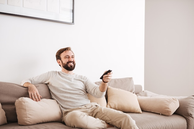 Portrait of a happy man holding remote control