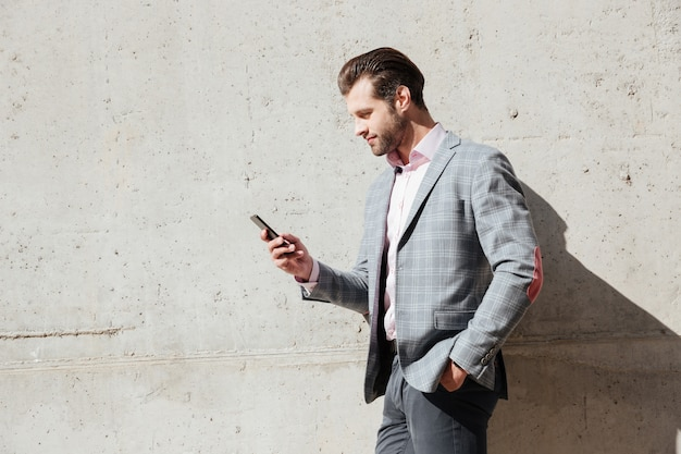 Portrait of a happy man in jacket holding mobile phone