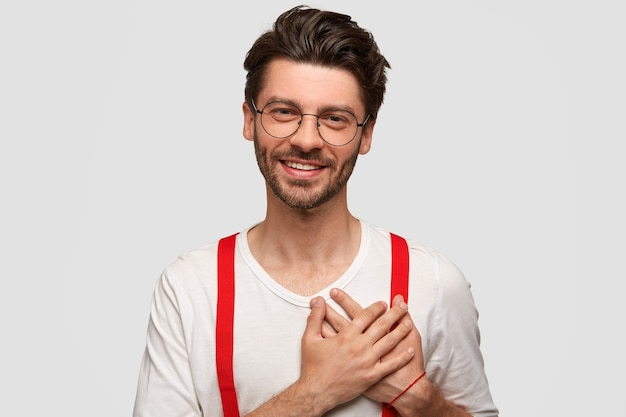 Portrait of happy man keeps both palms on heart, appreciates something with big gratitude, dressed in stylish outfit, has friendly smile, isolated over white wall. people, emotions, positivity