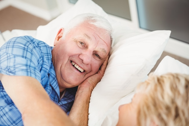 Portrait of happy man lying with his wife on bed