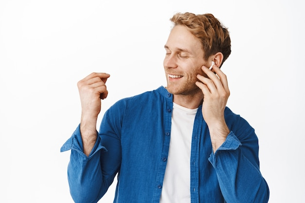Portrait of happy man smiles and touches headphone while listens to music, snap finger and close eyes, relaxing with favorite songs, stands over white wall