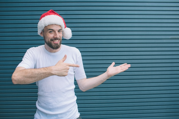 Portrait of happy man standing and poiting to the right. he wears christmas hat. guy is looking on camera and smiling. isolated on striped