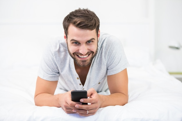 Portrait of happy man using mobile phone on bed