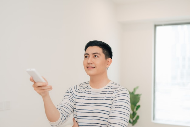 Portrait of happy man using remote control to operate air conditioner