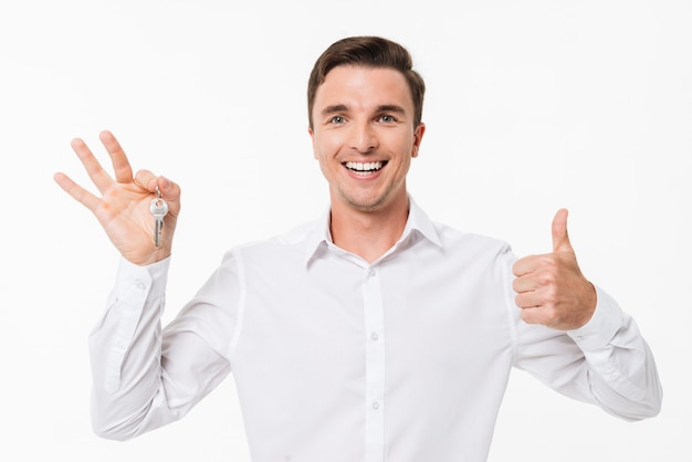 Portrait of a happy man in white shirt holding keys