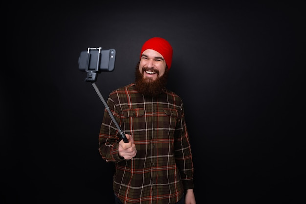Portrait of a happy man with beard making selfie photo with stick isolated on a dark wall