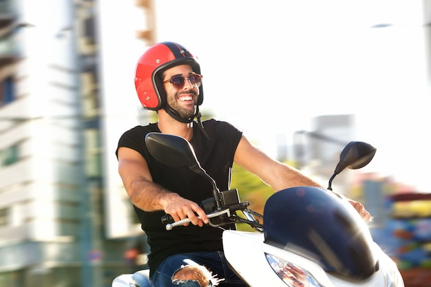 Portrait of happy man with helmet on motorcycle ride in city