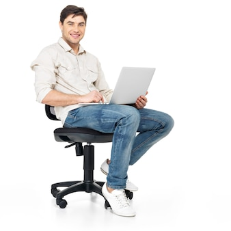 Portrait of happy man working on laptop sits on the chair