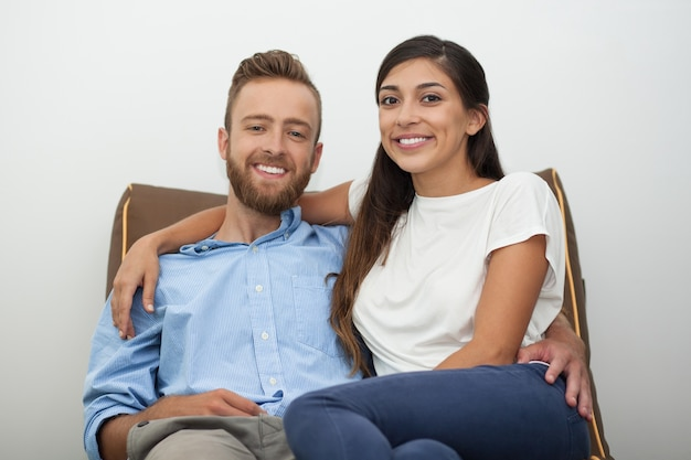 Portrait of happy married couple sitting on coach