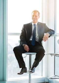 Portrait of a happy mature businessman sitting on stool