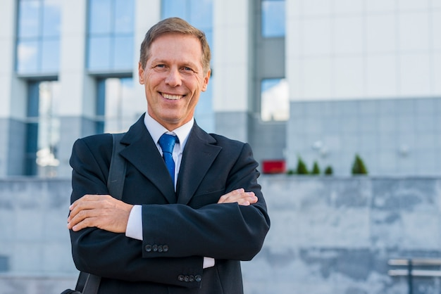 Portrait of a happy mature businessman with folded arms