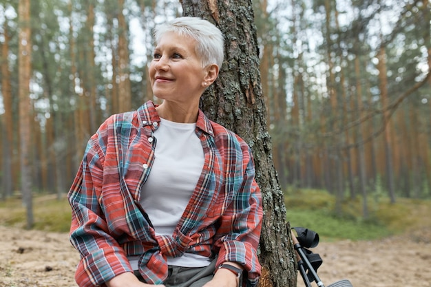 Portrait of happy mature female with short blonde har sitting under tree in plaid shirt looking around, admiring beautiful pine forest, having relaxed facial expression, smiling. hiking and nature