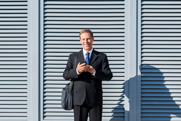 Portrait of a happy mature man using mobile phone