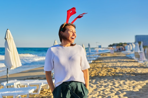 Portrait of happy mature woman in holiday ears on the beach