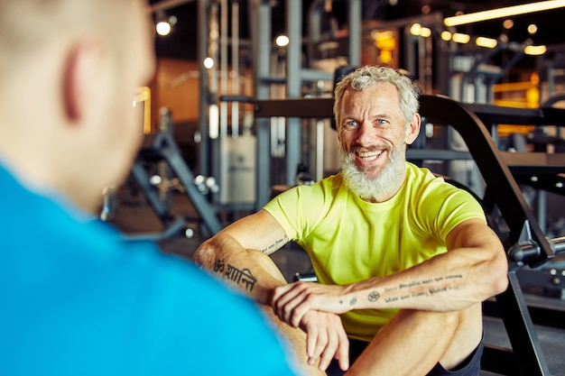 Portrait of a happy middle aged man discussing training results with fitness instructor or personal