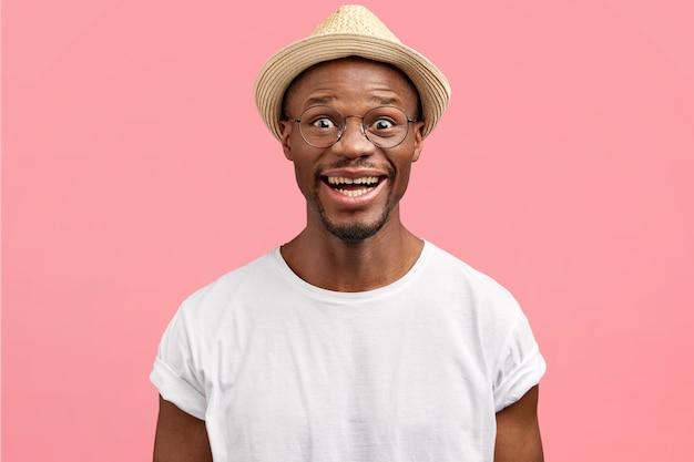 Ritratto di felice uomo di mezza età con pelle sana, vestito con maglietta bianca casual e cappello di paglia, isolato sopra il muro rosa