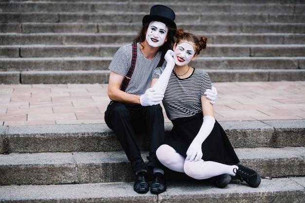 Portrait of a happy mime couple sitting on staircase