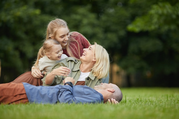 Portrait of happy modern family lying on green grass in park while having fun together outdoors