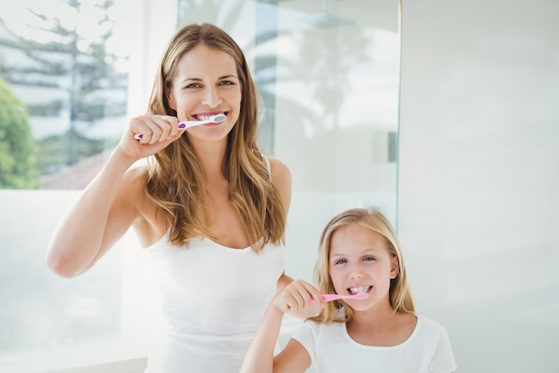 Portrait of happy mother and daughter brushing teeth