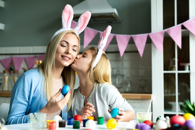 Portrait of happy mother and daughter during preparing for easter. they wearing bunny ears. daughter kissing her mother with love