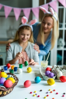 Portrait of happy mother and daughter during preparing for easter. they wearing bunny ears. soft focus.