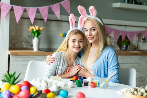 Portrait of happy mother and daughter hold hands posing during preparing for easter. they wearing bunny ears.