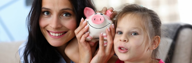 Portrait of happy mother and daughter shaking piggy-bank with coins. little girl and her mom posing at home. investment in future and saving money concept