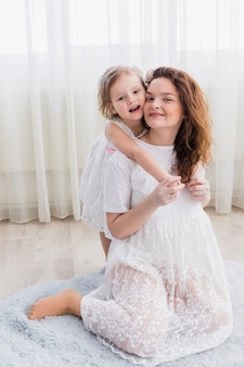 Portrait of happy mother and daughter sitting on soft carpet looking at camera