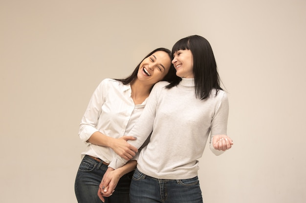A portrait of a happy mother and daughter at studio on gray