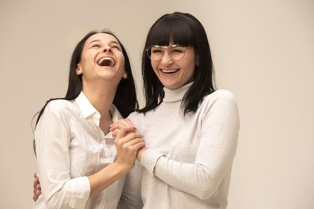 Un ritratto di una felice madre e figlia in studio su grigio