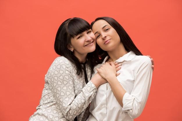 Un ritratto di una madre e una figlia felici in studio su sfondo corallo vivente. colori alla moda. le emozioni positive umane e il concetto di espressioni facciali