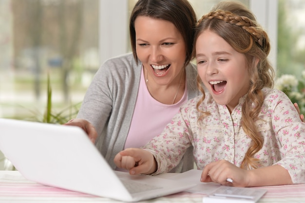 Portrait of happy mother and daughter using laptop