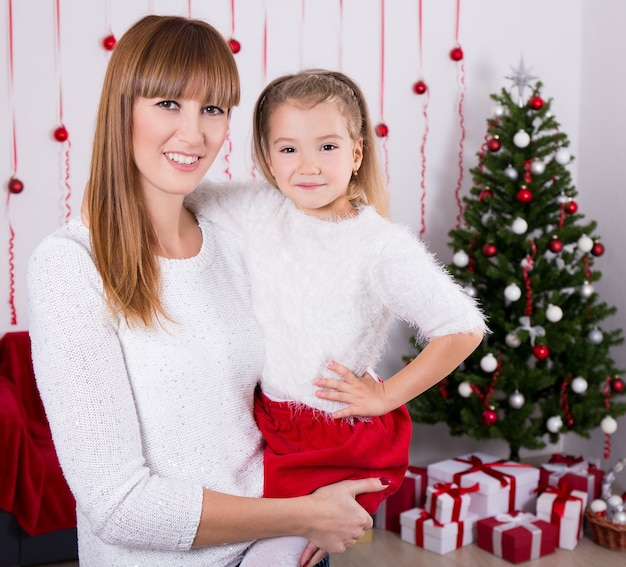 Portrait of happy mother and daughter with christmas tree at home