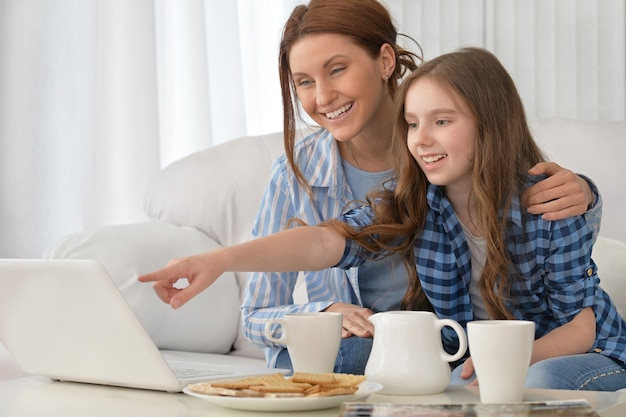 Portrait of a happy mother and daughter with laptop