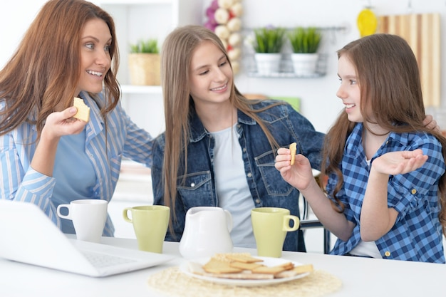 Portrait of happy mother and daughters with laptop