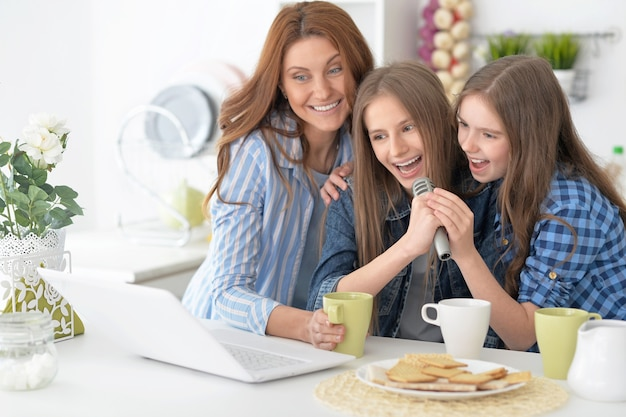 Portrait of a happy mother and daughters with laptop
