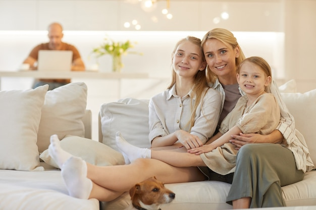 Portrait of happy mother embracing two daughters while posing together sitting on couch in cozy home interior with father