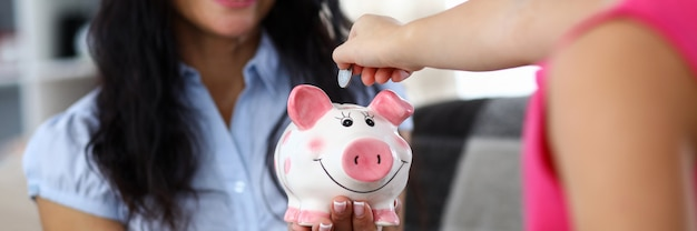 Portrait of happy mother holding pink funny piggy bank. little child putting money into thrift-box. mom looking at daughter with happiness. money savings concept