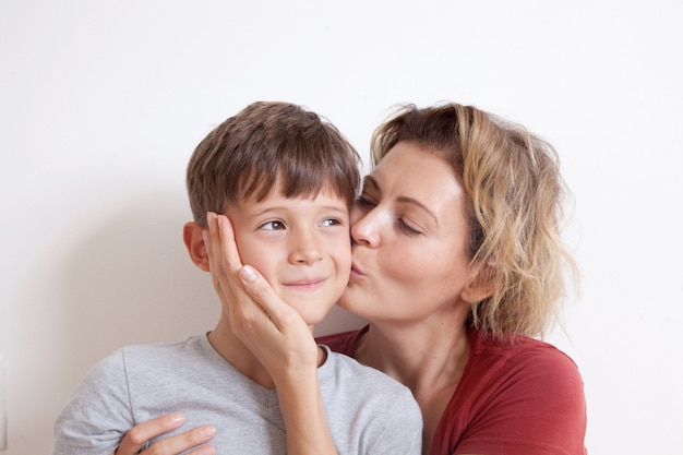 Portrait of happy mother kissing her cute blond boy on a light wall. happy family concept.