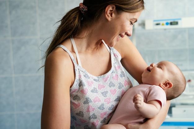 Портрет счастливая мать, играющая и целующаяся со своим младенцем. семья, люди, детское понятие