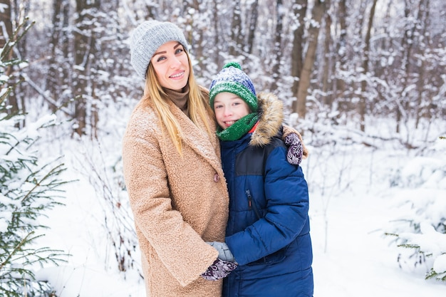 Portrait of happy mother with child son in winter outdoors